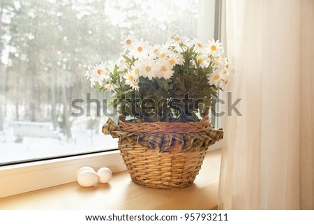 White eggs are in a basket with flowers on a window sill in the house