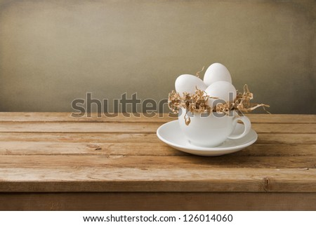 White eggs in coffee cup on wooden table