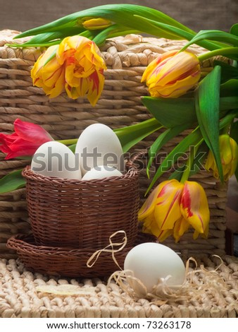 white eggs in small brown  and spring tulips basket on straw tray