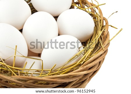 Photo of white eggs in the basket on white background