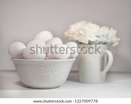White eggs in white bowl with white carnations in white mug.