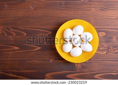 white eggs in yellow plate on brown table top view on the left space for text