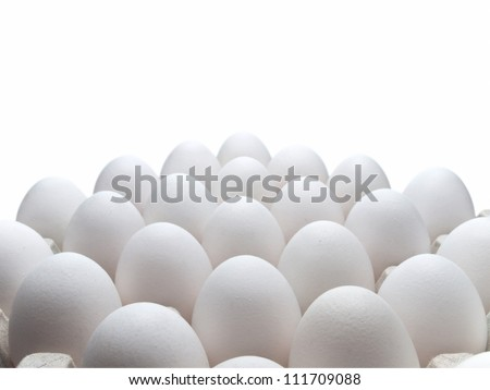 White eggs of a hen in harmless, cardboard packing on a white background.
