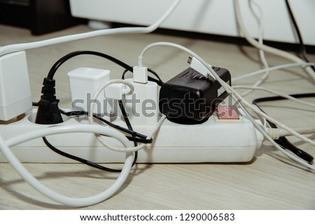 White electric power supply with plugs inserted. Electrical sockets with plugs. Problem with electricity, overuse of electricity. No savings in electricity.