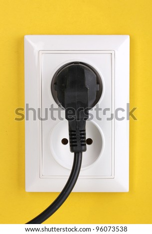 White electric socket with plug on the wall - stock photo