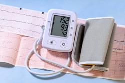 White electric tonometer on a Cardiogram and high pressure value. Medicine concept.