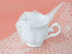 White elegant tea cup half packaged with white transparent bubble wrap on a pink background. Material for packing fragile items for safe transportation. Close-up.