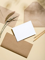 White empty card with stationery set of envelopes, notebook, pencils. Blank card styled mockup with hard light and shadow. To do list, greeting card or writing a letter concept.