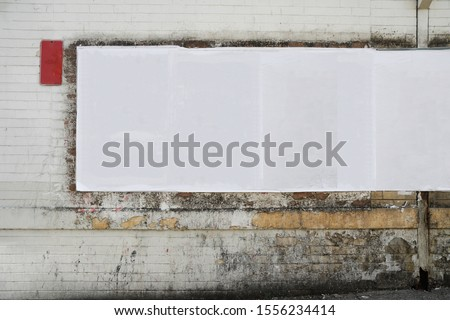 White empty creased street posters glued to grungy urban stained brick wall