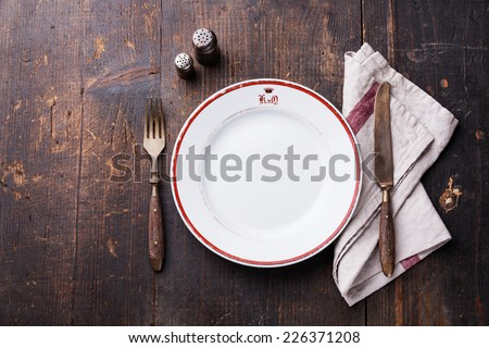 White empty plate and fork and knife on wooden texture background