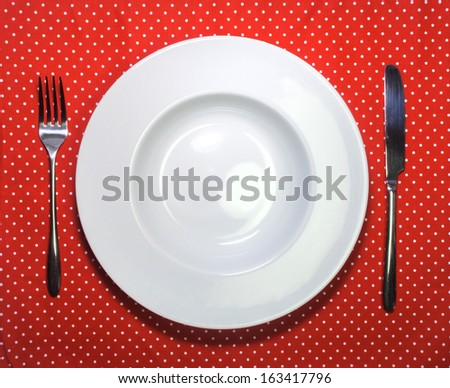 White empty plate, fork and knife on red cloth with polka dots