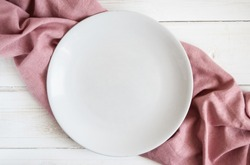 White empty plate on a pink napkin and white wooden table