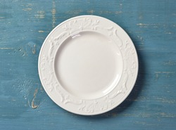 white empty plate on blue wooden table, top view