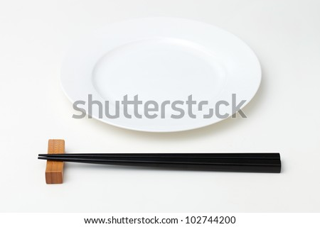 White empty plate with chopsticks - stock photo