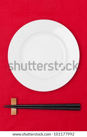 White empty plate with chopsticks on red tablecloth