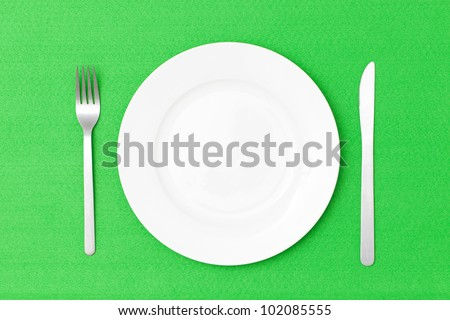 White empty plate with fork and knife on green table cloth - stock photo