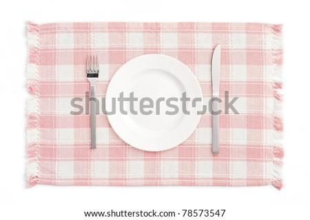 White empty plate with fork and knife on pink check mat