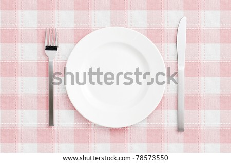 White empty plate with fork and knife on pink check mat - stock photo