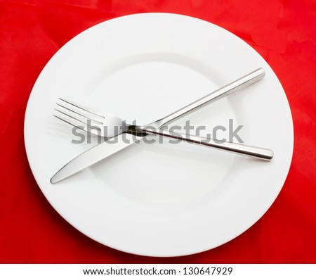 White empty plate with fork and knife on red