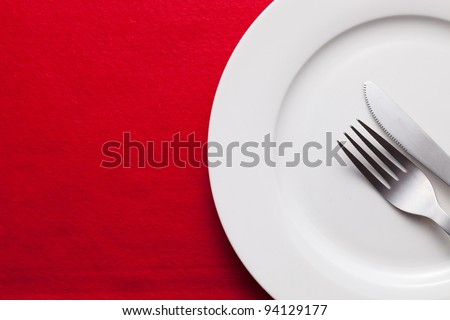 White empty plate with fork and knife on red tablecloth