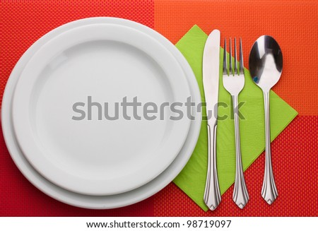 White empty plate with fork, spoon and knife on a red tablecloth