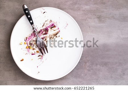 White empty plate with piece of cake leftovers from above on gray background. Copyspace for text