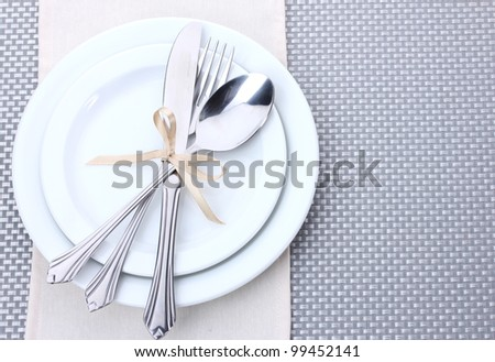 White empty plates with fork, spoon and knife tied with a ribbon on a grey tablecloth - stock photo