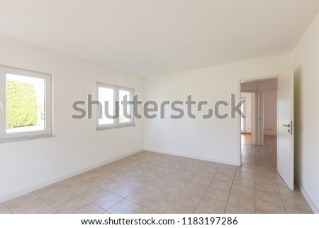 White empty room with tiles and windows, nobody inside