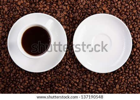 white empty saucer and cup of coffee at coffee beans