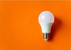 White energy saving light bulb isolated on an orange background with copy space. Concept of eco-friendly life. Minimal thing. LED white bulb, concept of new idea. Minimal think.