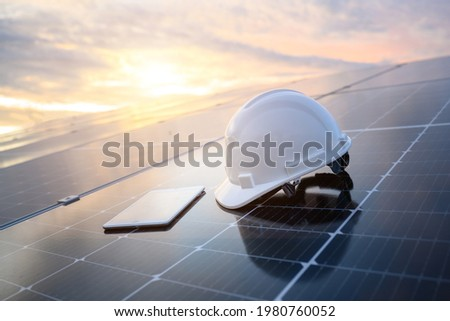 White engineer hard hat and a tablet placed on the solar panel At a photovoltaic power station working on solar energy storage in the industry. Foto stock ©