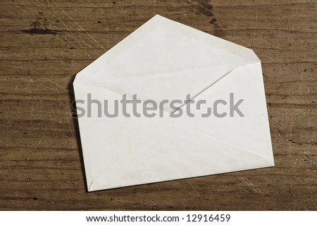 White envelope on wooden table, open, studio shot.