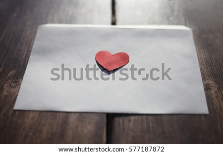 White envelope with red heart shaped figure cut from paper.Hand crafted love letter for Saint Valentines Day celebration.Celebrate 14 February with handmade postcard.Send post cards to people you love #577187872