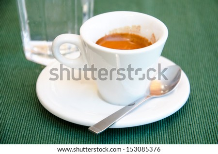 White espresso cup and a glass of cold water standing on the green textile tablecloth