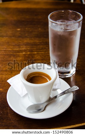 White espresso cup with glass of cold water standing on the wooden table