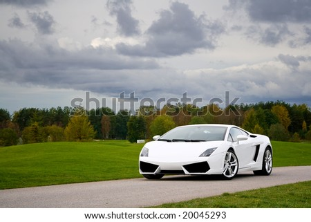 White exclusive supercar on a narrow road near golf field