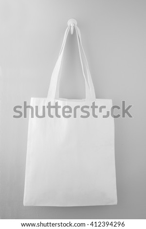 White fabric bag hanging on the gray wall