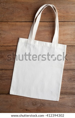 White fabric bag on wooden table