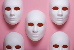 White face masks composition on pink background, fake identity or multiple personalities