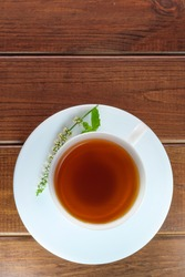 White faience cup with black tea on a saucer on a brown wooden background close-up