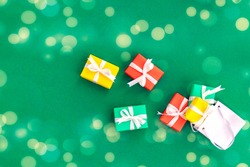 White fallen paper bag with scattered gifts. Red, green and yellow gifts in a shopping bag on a green background with bokeh. Christmas and Xmas gift concept. Copy cpase. Top view. Flat lay