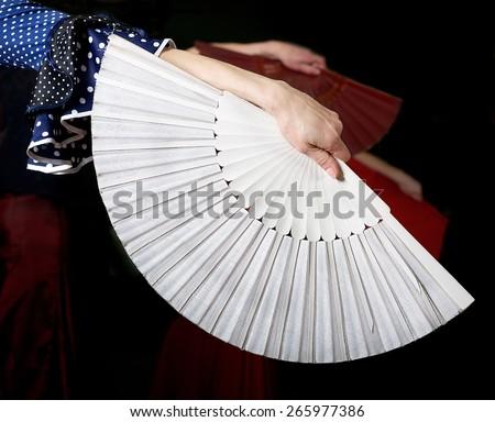 White fan and fragment of woman hand in flamenco performance, fragment photo of flamenco dancer, spanish fan, flamenco