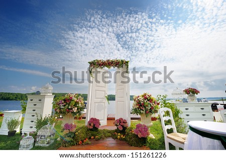 White fancy door as a wedding arch decorated with flowers