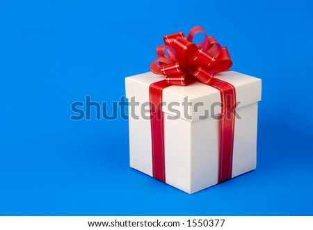 White fancy gift box with red ribbon - birthday present concept - isolated on blue background