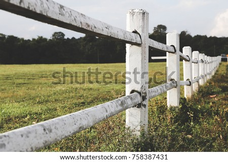 White farm fence boundary on mountain with grass field. Boundary separate concept. #758387431