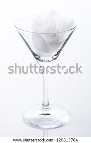 White feather of bird in cocktail glass