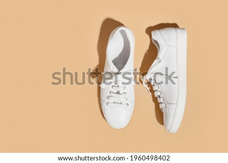 White female gumshoes on a beige background with copy space. View from above. Copy space. Foto stock ©