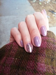 White Female  Hand  with  Lilac Gel Nail Polish Manicure, Checkered Pink and Moss Green Tweed Jacket Sleeve