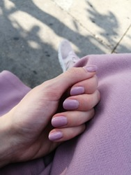 White Female Hand with Pale Pink Shellac Manicure, Matching Pink Skirt, Sneakers