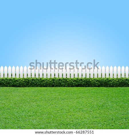 White fence and green grass on blue sky - Shutterstock ID 66287551